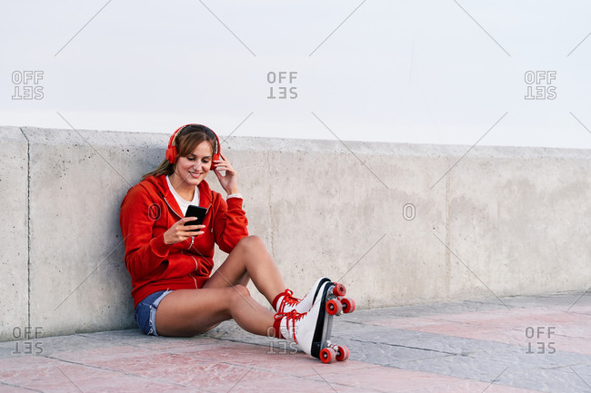 Relaxed female in roller skates sitting on embankment and listening to music in headphones while enjoying weekend