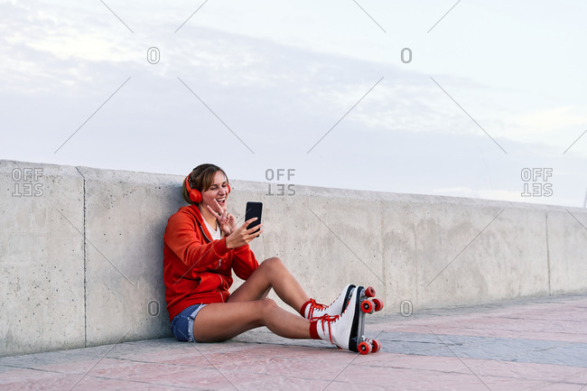 Side view of relaxed female in roller skates sitting on embankment and listening to music in headphones while taking selfie on smartphone enjoying weekend