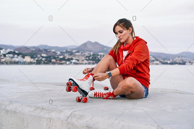 Peaceful female sitting on embankment and tying shoelaces while preparing for riding roller skates