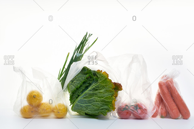 Still life with food in plastic bags backlit on white background