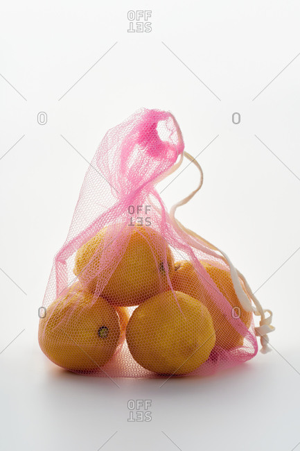 Still life with lemons in pink net textile bag backlit on white background