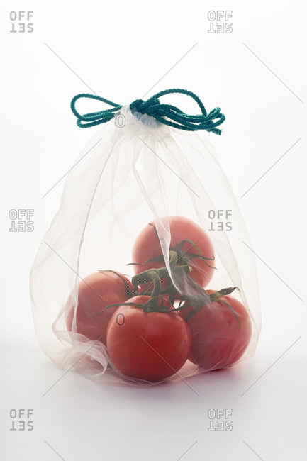 Still life with tomatoes in net mesh bag back lit on white background