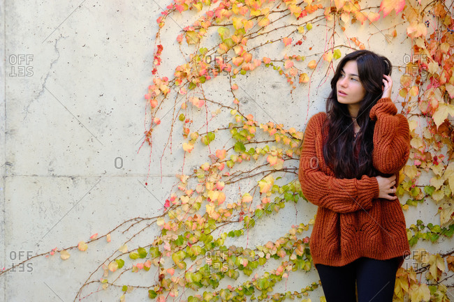 Pensive young long haired brunette in warm knitted sweater standing near stone wall with colorful autumnal foliage and looking away