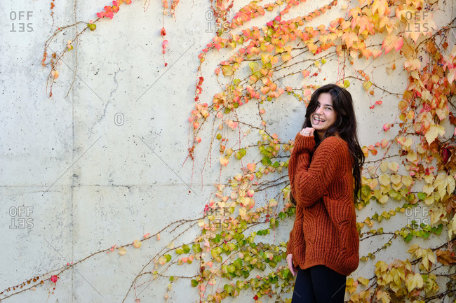Cheerful young long haired brunette in warm knitted sweater standing near stone wall with colorful autumnal foliage and looking at camera