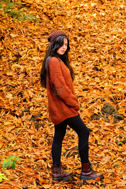 Full length of young serious brunette female in red knitted sweater and jeans standing on fallen leaves and enjoying sunny autumn day in forest