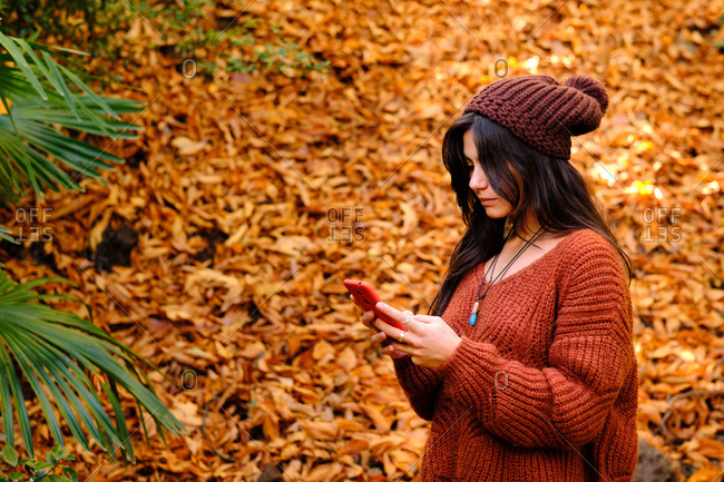 Side view of young brunette female in warm red knitted pullover browsing mobile phone while standing in autumn park with fallen colorful leaves
