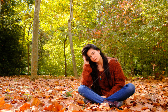 Full length of young serious brunette female in red knitted sweater and jeans sitting on fallen leaves and enjoying sunny autumn day in forest
