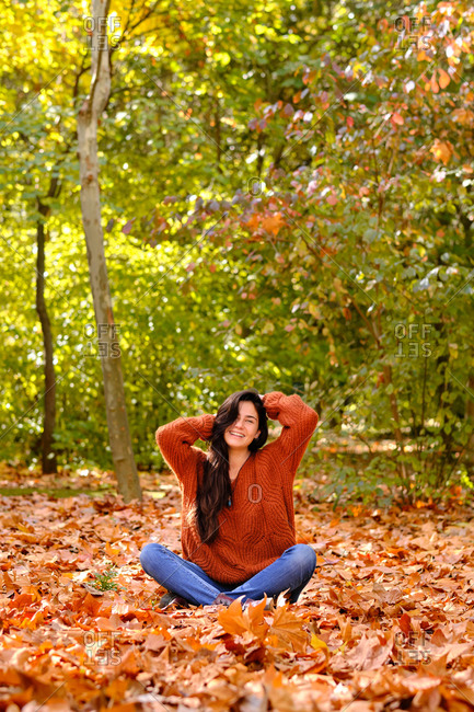 Full length of cheerful young female in red knitted sweater and jeans sitting on fallen leaves and enjoying sunny autumn day in forest