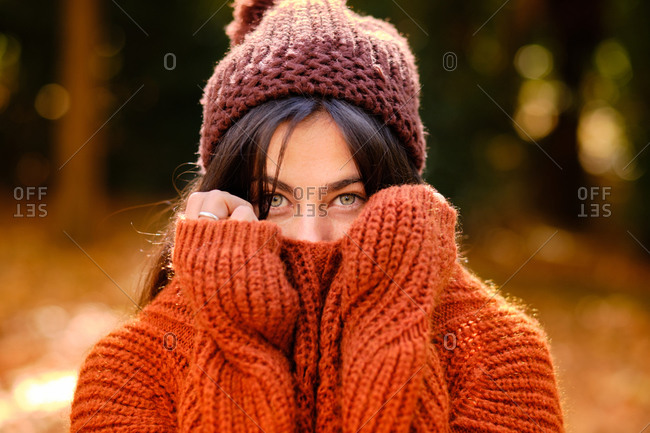 Young female in knitted hat covering face with warm sweater while standing in forest in cold autumn day