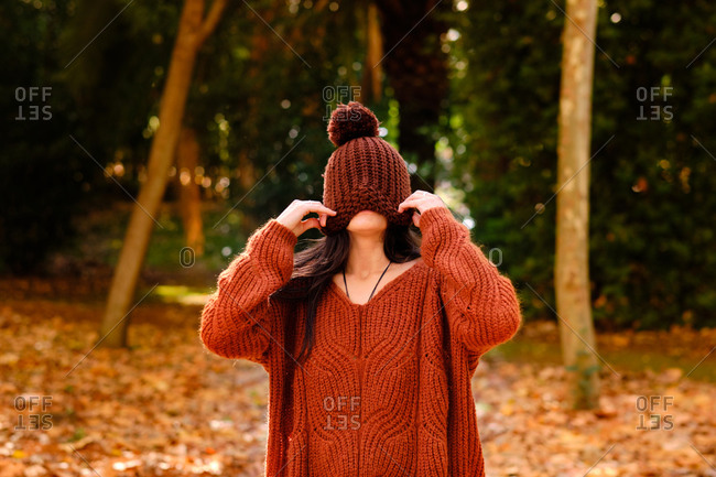 Unrecognizable female in knitted hat covering face wearing a warm sweater while standing in forest in cold autumn day