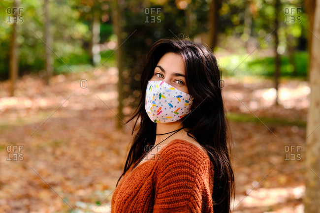 Side view of confident young long haired brunette in colorful cloth protective mask for coronavirus prevention looking at camera while standing against blurred background of autumnal park