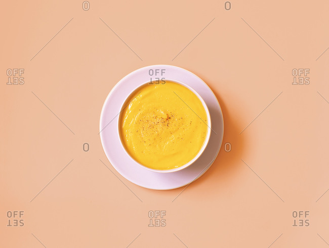 Top view of bowl of appetizing pumpkin cream soup placed on pink background in studio