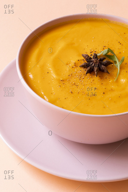 Bowl of appetizing pumpkin cream soup placed on pink background in studio