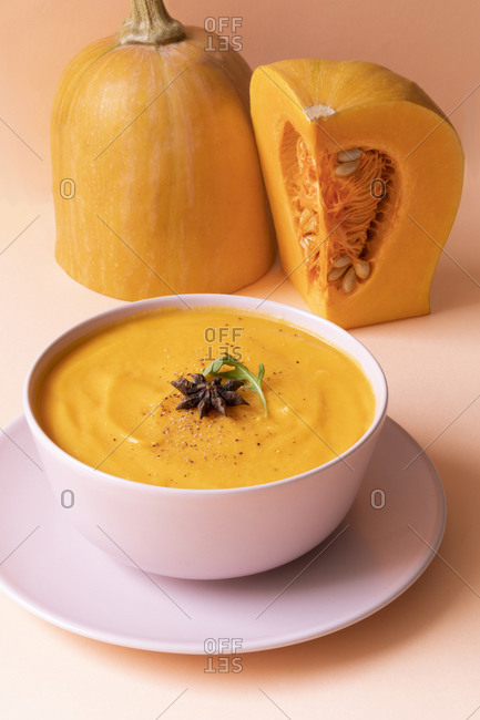 Bowl with delicious pumpkin cream soup and fresh raw pumpkin arranged on pink background