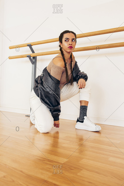 Low angle of young female in trendy clothes crouched in dance studio and looking away