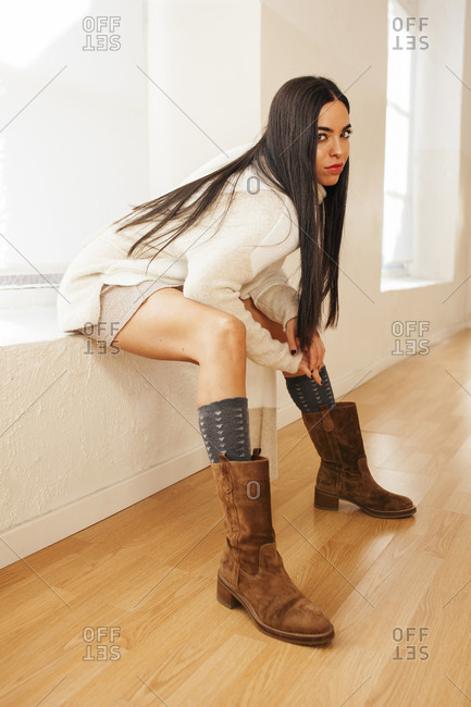 Side view of determined female wearing stylish clothes sitting on windowsill and looking at camera