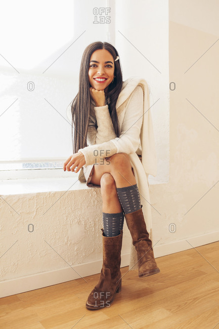 Front view of determined female wearing stylish clothes sitting on windowsill and looking at camera