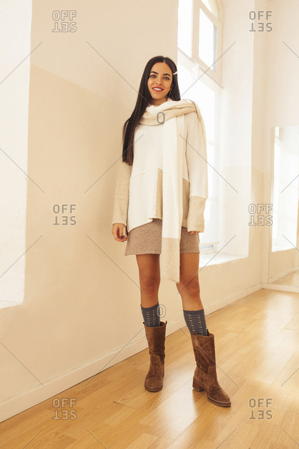 Young female wearing stylish apparel standing in bright room and looking at camera