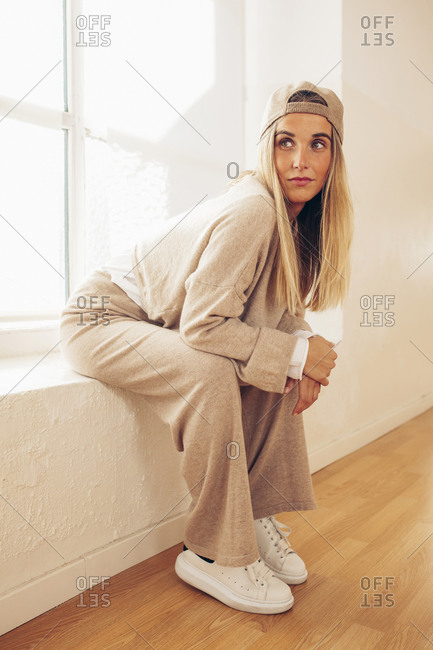 Side view of determined female wearing stylish clothes sitting on windowsill and looking away