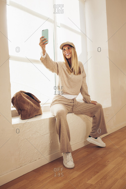 Cheerful fashionable female sitting on windowsill and taking selfie on smartphone while having fun and smiling