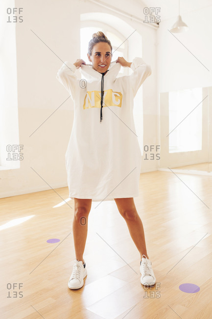 Front view of female in trendy dress and sneakers standing in spacious room and looking away