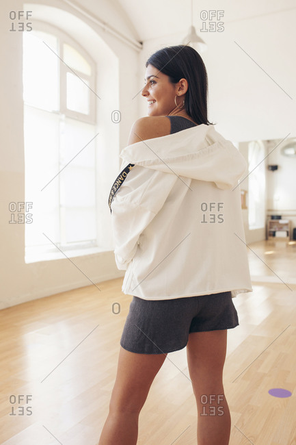Back view of young female in street style clothing and in hood standing in bright room and looking away