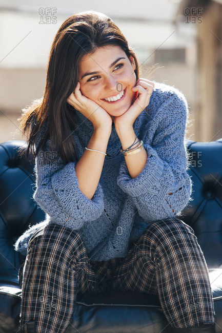 Delicate charming female in casual wear sitting on sofa and leaning on hands while looking away