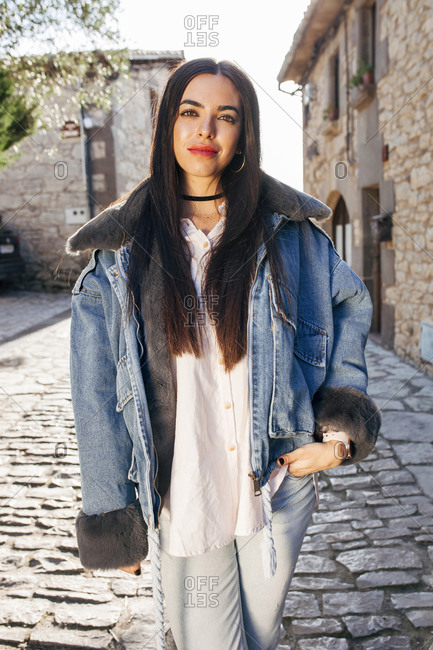 Stylish female in warm denim jacket standing on street in ancient town and looking at camera