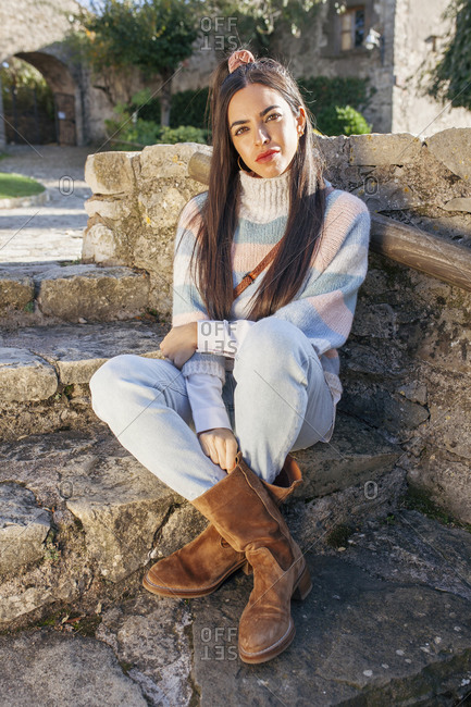 Peaceful female in trendy apparel sitting on shabby stone steps on street during stroll in ancient city
