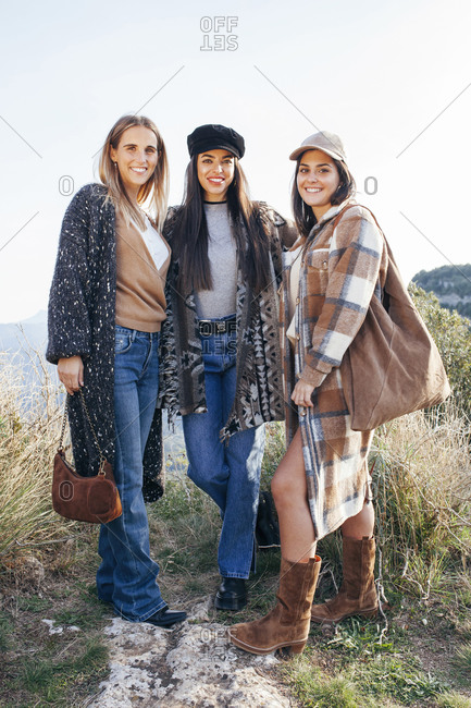 Company of positive female friends in stylish casual clothes cuddling together while standing on hill in mountains