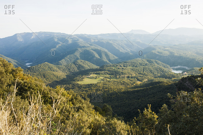 Scenic landscape of mountain range covered with green forests on sunny day in summer