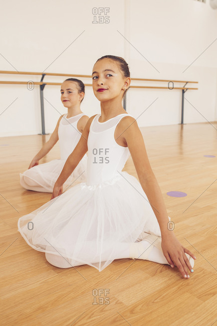Graceful teenage ballerinas in tutu sitting on wooden floor in dance studio and stretching looking away