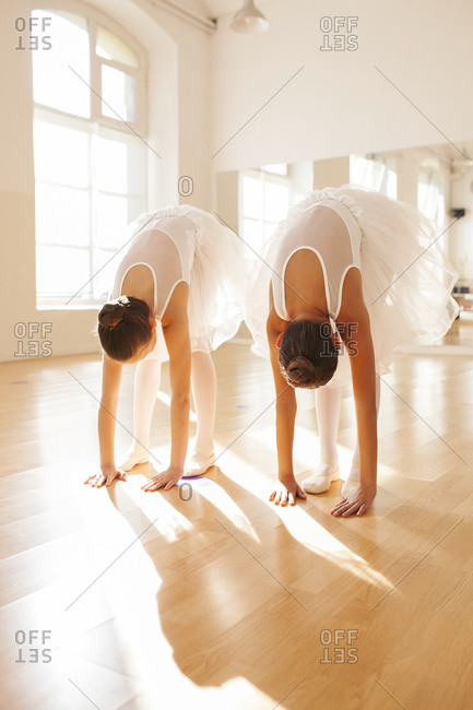 Unrecognizable teenage ballet dancers in tutu stretching in dance studio and doing forward bend