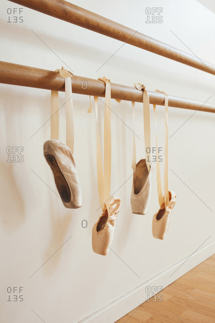 Pairs of silk pointe shoes hanging on ballet barre in bright dance studio
