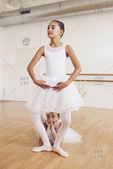 Adorable teen ballerinas in tutu dancing gracefully in bright studio while looking away