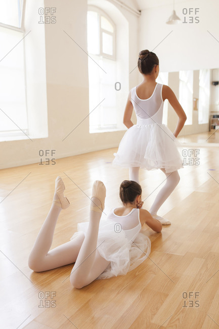 Back view of unrecognizable adorable teen ballerinas in tutu dancing gracefully in bright studio