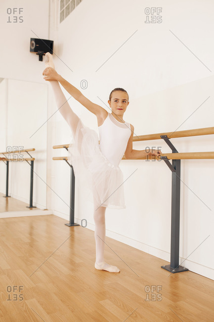 Charming teenage ballerina in pointe shoes stretching legs near ballet barre in dance hall