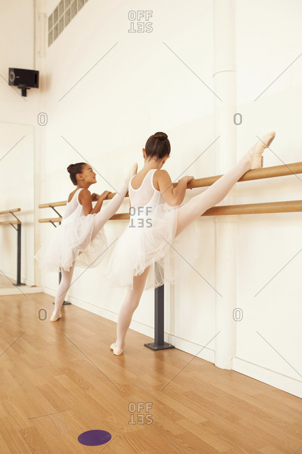 Low angle of charming teenage ballerinas in pointe shoes stretching legs near ballet barre in dance hall