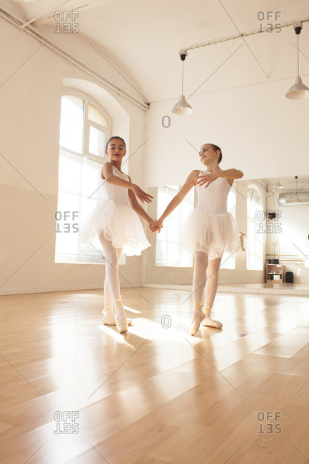 Smiting teenage ballet dancers rehearsing together in bright dance studio