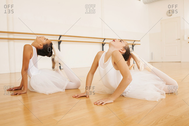 Side view of teenage ballet dancers in tutu and pointe shoes stretching body during lesson in dance hall looking up
