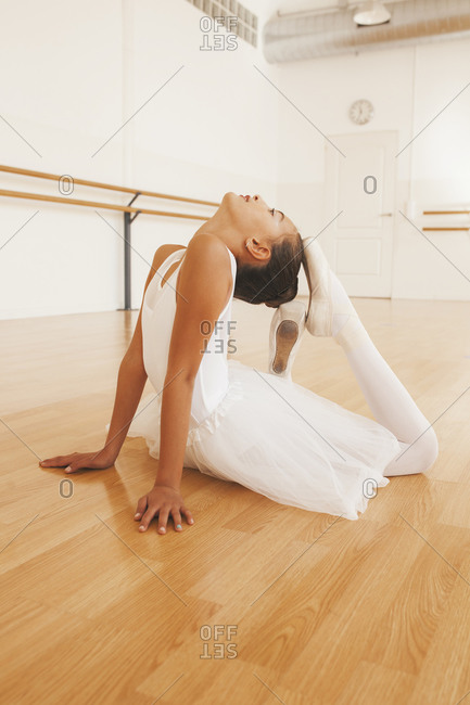 Side view of teenage ballet dancer in tutu and pointe shoes stretching body during lesson in dance hall looking up