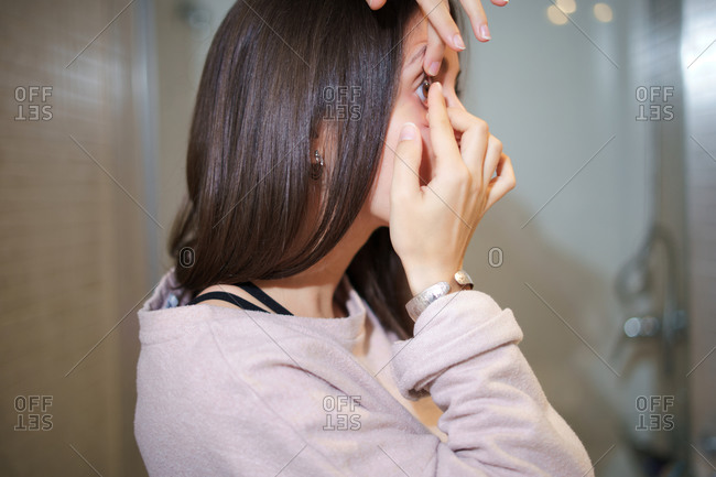 Side view of female putting on contact lens on eye while standing in bathroom and looking in mirror