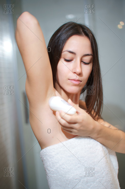 Side view of delicate female in towel standing in bathroom and applying antiperspirant on armpit after taking shower