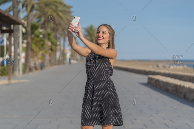 Charming female in dress standing on embankment and taking selfie with cellphone on sunny day