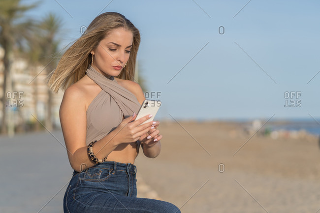 Confident female in stylish summer outfit sitting on embankment near beach and chatting on social media via mobile phone