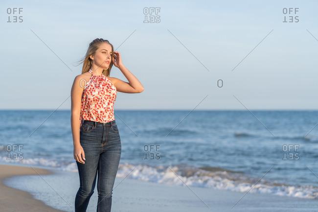 Female traveler walking along wet sandy coast and enjoying scenery of sea on sunny day