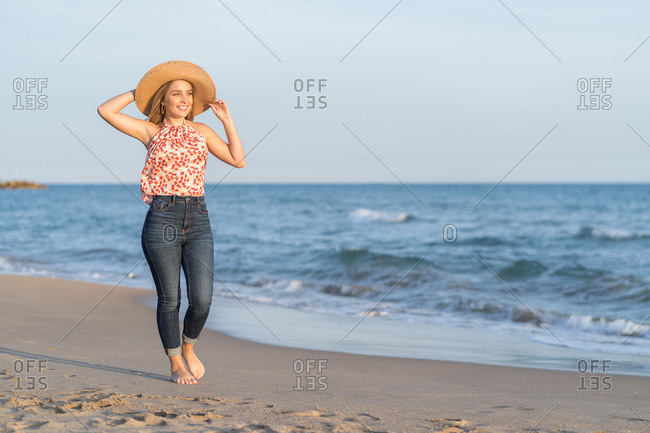 Content female traveler in straw hat walking along wet sandy coast and enjoying scenery of sea on sunny day
