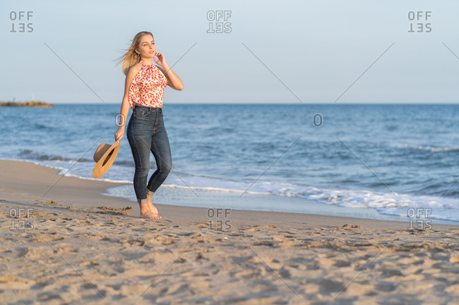 Serious female traveler in straw hat walking along wet sandy coast and enjoying scenery of sea on sunny day