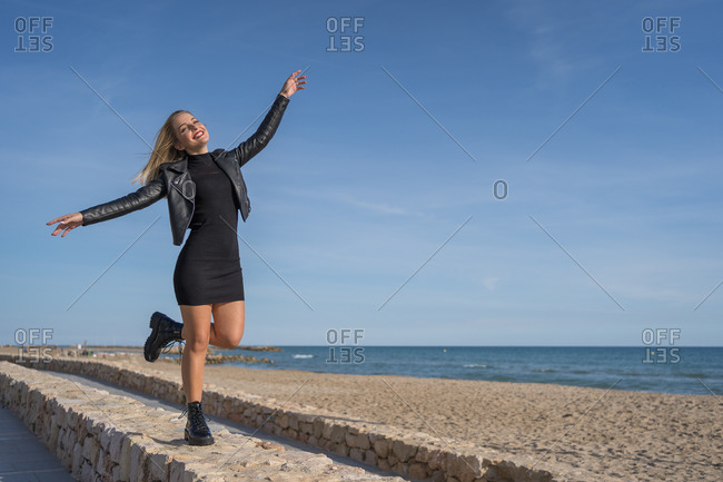 Carefree female in stylish wear enjoying sunny weather and freedom with closed eyes and outstretched arms at seaside