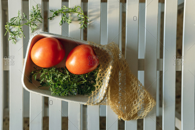 Top view of fresh organic bio red tomatoes with green herbs in tray with eco sack placed on white table